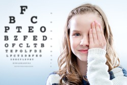 Close up portrait of girl reviewing eyesight closing eye with hand.Out of focus test chart in background.