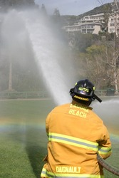 LAGUNA BEACH, CA - FEB 19: Firefighter recruit sprays water during fire fighting drills at the local Fire Department training area on February 19, 2009 in Laguna Beach, California.