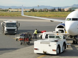 Loading suitcases and other cargo  in an airplane on the runway