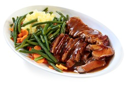 Platter of sliced roast beef with gravy, mashed potatoes, string beans and carrots.  A hearty meal.