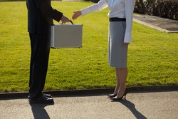 Man handing woman briefcase