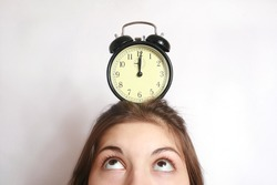 The image of an alarm clock costing on a head of the girl.