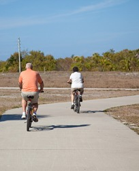Rear view of a senior couple riding their bicycles.  Focus on the husband, in the foreground.
