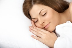 Portrait of the beautiful sleeping woman in white bed