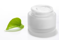 Pot of moisturizing face cream with green leaf on white background