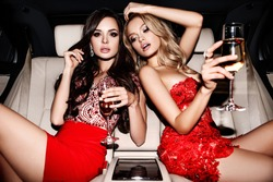 two girls in red dresses have a drink in a car