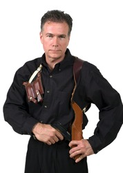 Mature, handsome, white male dressed in black on an isolated background wearing a shoulder holster armed with an automatic pistol.