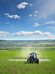 Farming tractor plowing and spraying on field vertical