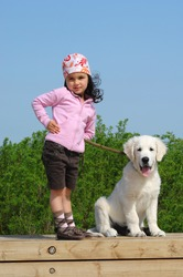 little girl with a Golden retriever puppy posing near the beach