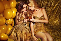 ladies in golden dress clinking two glasses of wine