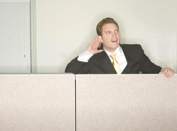 Businessman listens as he puts his hand to his ear while he hears the conversation from his office cubicle