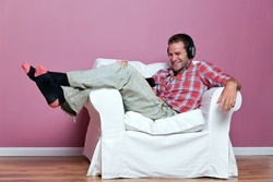 Male in casual clothing relaxing on an armchair wearing headphones whilst watching and listening to a music video on his media player.