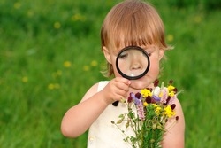 Cute little girl looking at bouquet of field flowers through magnifying glass
