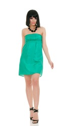 Beautiful fashion model in green mini dress isolated over white background
