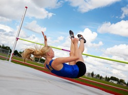 A young, athlete clearing the bar during a high jump event, in track and field.