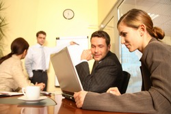 A business team of two men and two women work together with a laptop and a flip chart in a conference room to prepare a new business proposal for a client.
