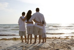 Family standing on a beach, looking towards water