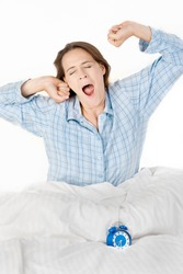 A woman in pyjamas yawning and stretching.