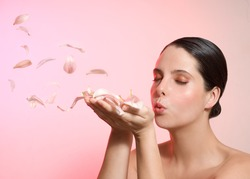 Beauty woman blowing rose petals