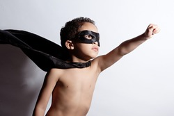 Portrait of a young, mixed race boy dressed as a superhero.