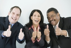 Business team giving thumbs up sign