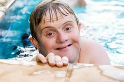 Close up face shot of handicapped boy in swimming pool.