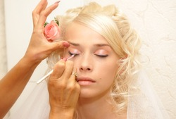 Young bride doing make up