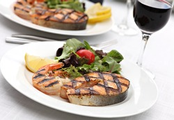 Grilled salmon steak with shrimps and fresh summer salad mix