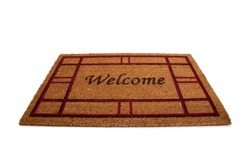 "A mat or carpet with the word ""Welcome"" printed on it.  Hospitality"
