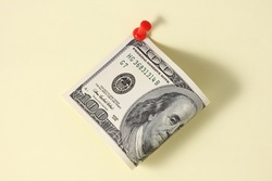 One hundred dollar bill with red push pin