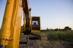 Excavator overlooking farmland with space for copy
