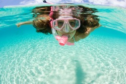 beautiful woman enjoys snorkeling in tropic waters
