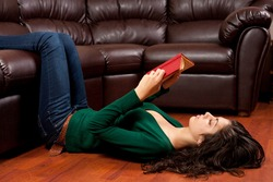Beautiful young ethnic lady reading a vintage book on a leather sofa