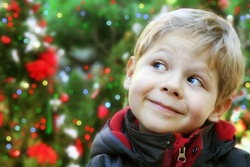 Five year old boy portrait outside with decorated Christmas trees