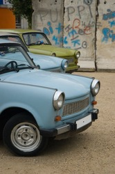 East-German plastic vintage cars parked near Berlin wall