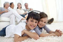 Children lying on carpet with their parents and grandparents in sofa at home