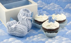 A pair of crocheted blue baby booties, a gift box and delicious chocolate cupcakes with vanilla frosted and baby carriage decoration, baby shower gifts, vertical with copy space