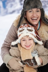 Portrait of happy mother and child holding cup of hot tea in snow on a cold winter day laughing, smiling.