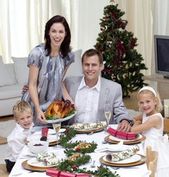 Parents and children celebrating Christmas dinner with turkey at home