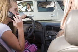 A teenage girl using her phone while driving and is going to be in a accident.