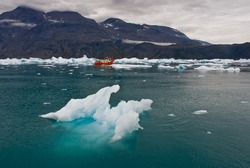 Narsarsuaq Icefjord, Greenland. Iceberg and Icy waters with a small red boat in the background.