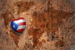 heart with national flag of puerto rico on a vintage world map crack paper background. concept