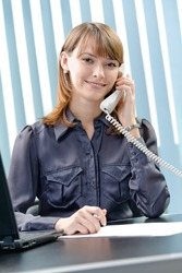 Happy businesswoman talking on phone at office