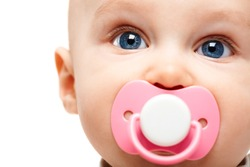 Face of adorable baby with pacifier in mouth looking at camera