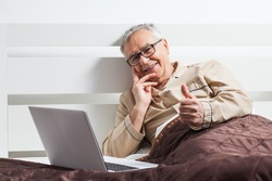 Happy senior man is lying in bed and using laptop
