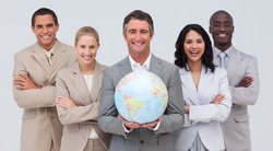Smiling Multi-ethnic business team holding a terrestrial globe