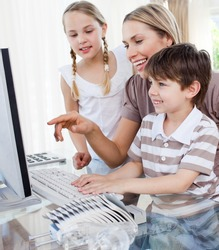 Happy mother and her children using a computer at home