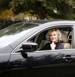 Blond pretty woman in black car