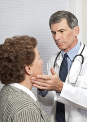 Male doctor feeling female patient's neck for swollen glands.