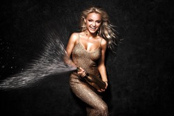 picture of a smiling golden haired lady spraying a bottle of champagne
